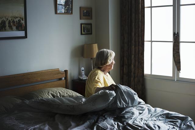 Stará žena sedí na posteli so sivými paplónmi.jpg