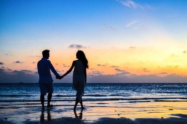 Žena a muž sa držia za ruky a idú po pláži