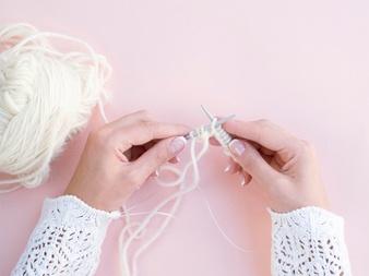 top-view-woman-crocheting-white-wool_23-2148264380